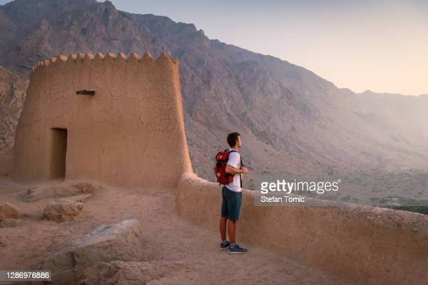 man visiting dhayah fort in north ras al khaima in the uae - ras al khaimah stock pictures, royalty-free photos & images