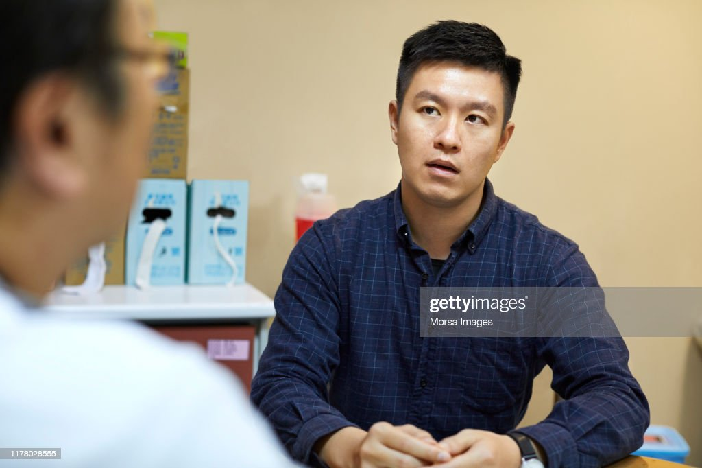 Man visiting doctor for routine checkup at clinic : Stock Photo