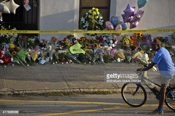 A man visits a memorial with flowers outside the Emanuel AME Church June 19 2015 in Charleston South Carolina US police arrested a white high school...