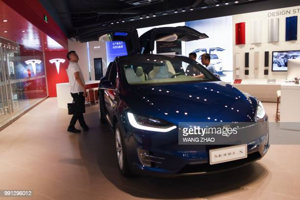 A man visits a Tesla showroom in Beijing on July 4 2018 Simmering trade tensions between the world's top two economies are set to erupt into a...