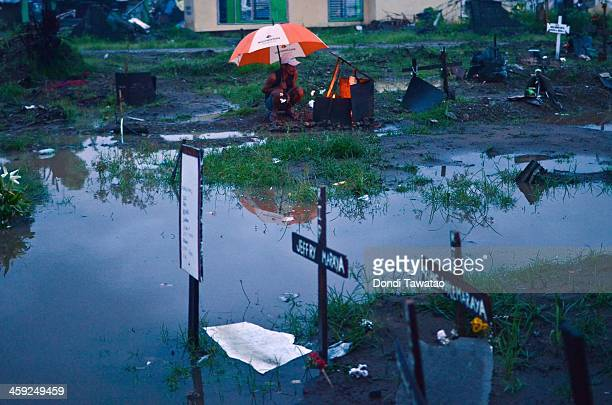 Man visits the grave of a loved one who perished during the typhoon at a flooded mass grave on Christmas eve on December 24, 2013 in Tacloban, Leyte,...