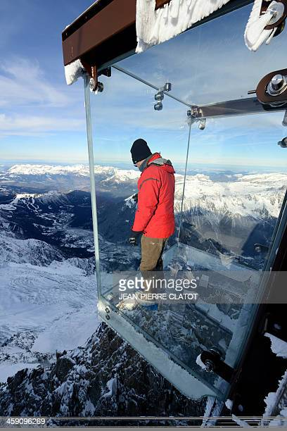 A man visits the 'Step into the Void' glass skywalk overlooking the French Alps on top of a 3842metre peak in Chamonix on December 23 2013 The...
