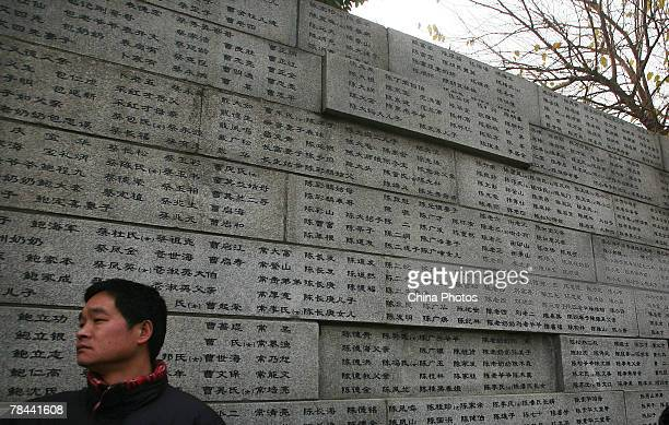 A man visits the wall engraved with names of victims who died in the Nanjing Massacre of 1937 during a ceremony to mark the 70th anniversary at the...