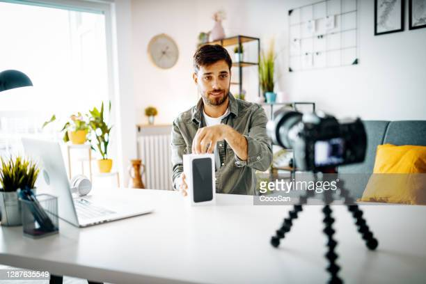 man vlogging from home, unboxing new smart phone on live stream - unboxing stock pictures, royalty-free photos & images