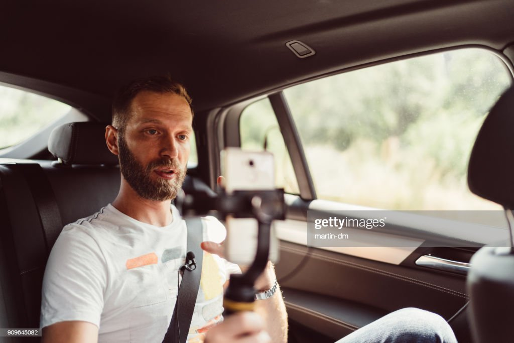 Man vlogging in taxi : Stock Photo