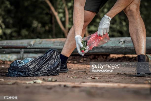 man volunteer wearing picking up trash and plastic waste in public park. young man wearing gloves and putting litter into black plastic bag outdoors. - altruism stock pictures, royalty-free photos & images