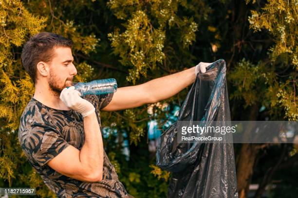 man volunteer wearing picking up trash and plastic waste in public park. young man wearing gloves and putting litter into black plastic bag outdoors. - altruismo foto e immagini stock