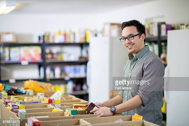 man volunteering at the food bank - food bank stock pictures, royalty-free photos & images