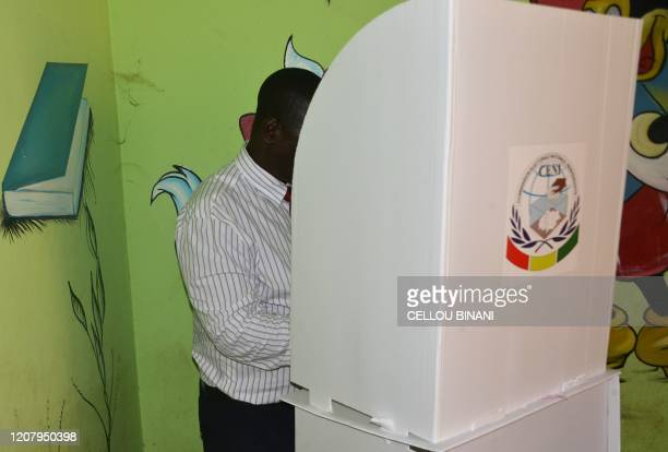 A man votes for the referendum and legislatives vote at a polling station in Conakry on March 22 2020 during a constitutional referendum vote Guinean...
