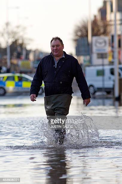 A man wades along a flooded street in Lowestoft in the east of England on December 6 2013 after a tidal surge hit locations along the east coast of...
