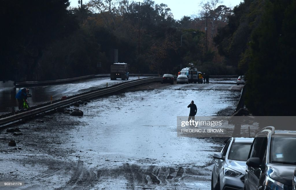 A man wades in a flooded section of the US 101 freeway near the San Ysidro exit in Montecito, California on January 9, 2018. Mudslides unleashed by a ferocious storm demolished homes in southern California and killed at least 13 people, police said Tuesday. /