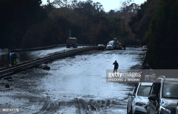 A man wades in a flooded section of the US 101 freeway near the San Ysidro exit in Montecito California on January 9 2018 Mudslides unleashed by a...