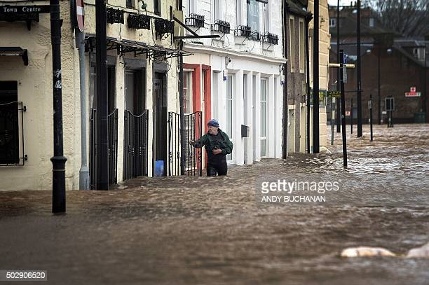 TOPSHOT A man wades in floodwater in a street in Dumfries southern Scotland on December 30 2015 after heavy rainfall brought by Storm Frank Storm...