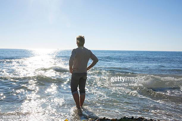 man wades in sea shallows, looks out to sea - rolled up pants stock pictures, royalty-free photos & images