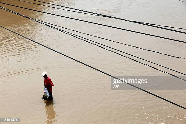 A man wades through a flooded street in Acapulco Guerrero state Mexico on September 26 2013 Authorities in Acapulco closed schools and evacuated...