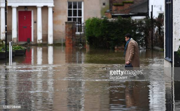 Man wades through flood water in Shrewsbury, western England after Storm Christoph brought heavy rains and flooding across the country on January 22,...
