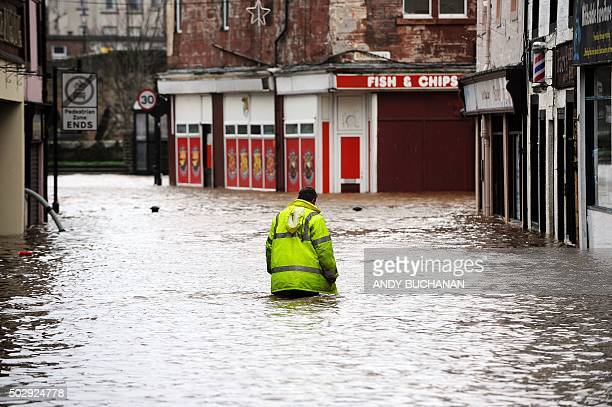 Man wades through floodwater in a street in Dumfries, southern Scotland, on December 30, 2015 after heavy rainfall brought by Storm Frank. Storm...