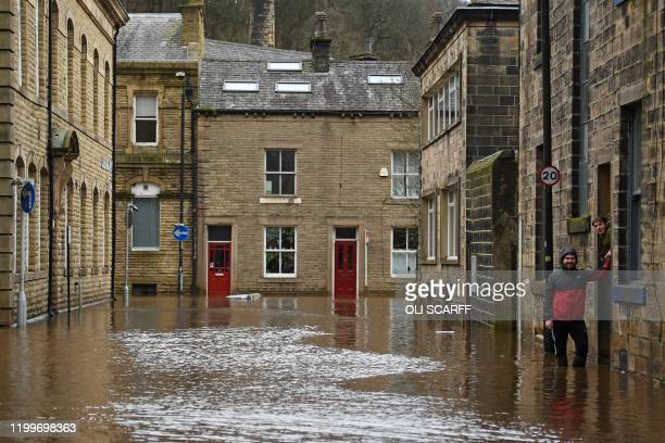 Man wades through floodwater in the streets of Hebden Bridge, northern England, on February 9 as Storm Ciara swept over the country. - Britain and...