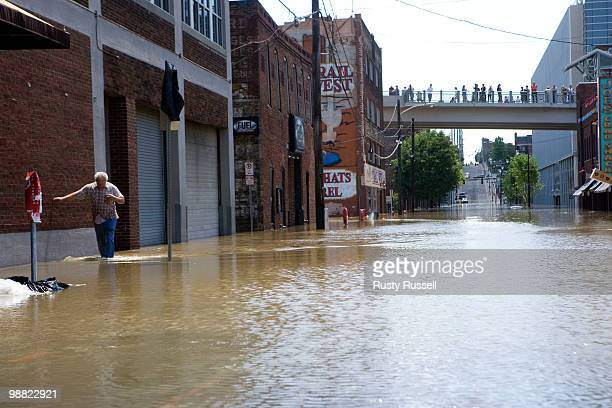 A man wades through floodwaters on a downtown sidewalk May 3 2010 in Nashville Tennessee More than 13 inches of rainfall fell over two days over...