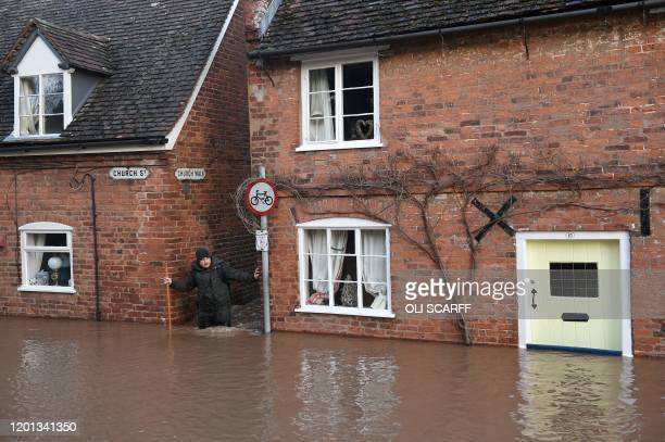 TOPSHOT A man wades through in flood water as he passes houses in Church Street in Tenbury Wells after the River Teme burst its banks in western...
