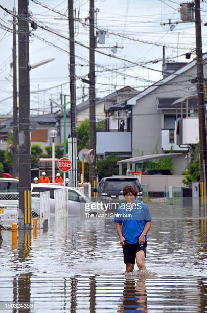 A man wades through knee deep flood water on August 14 2012 in Uji Kyoto Japan