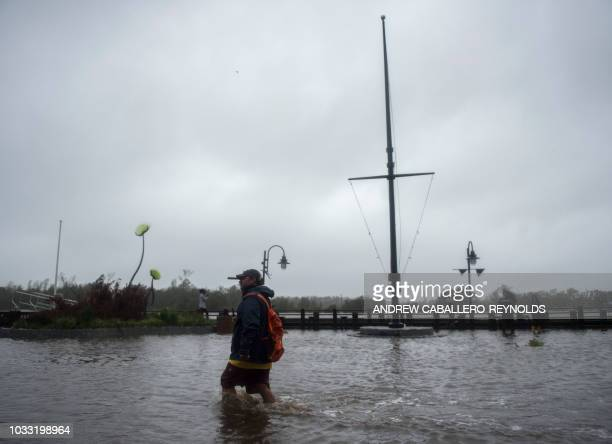 A man wades through rising flood waters on the Cape Fear River during Hurricane Florence in Wilmington North Carolina on September 14 2018 In the...