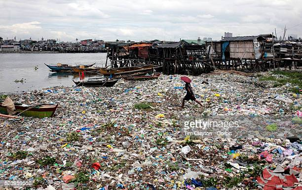 A man wades through the piles of trash in the Baseco area of Tondo on October 9 2008 in Manila the Philippines