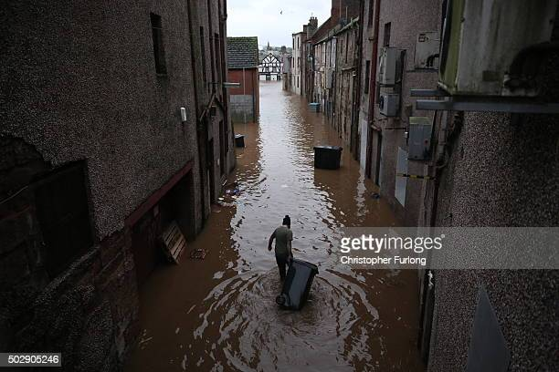 Man wades through the water with a rubbish bin as the River Nith bursts its banks on December 30, 2015 in Dumfries, Scotland. Severe flooding has...