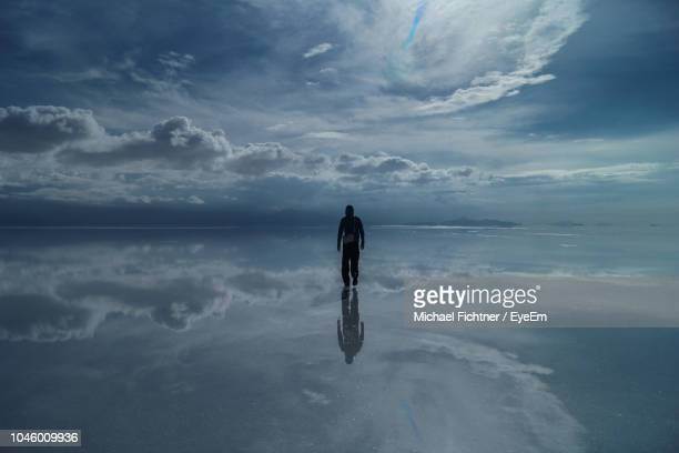 man wading in sea against sky - wading stock pictures, royalty-free photos & images