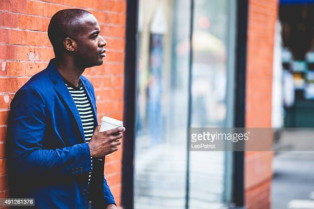 Man waiting against a brick wall in Soho New York
