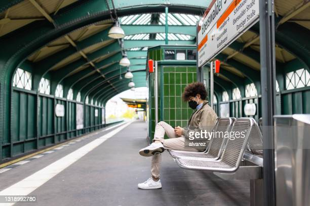 man waiting at metro train station using mobile phone - berlin stock pictures, royalty-free photos & images