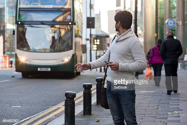 Mann warten Sie an der Bushaltestelle