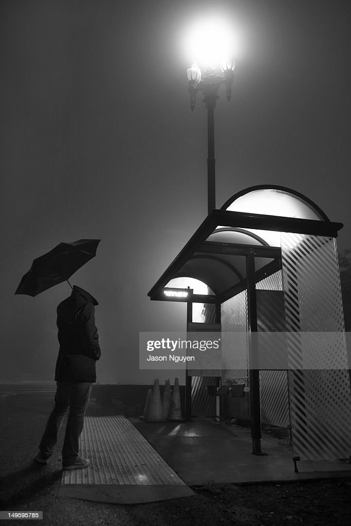 man waiting for bus with chance of rain ストックフォト getty images