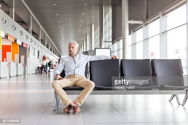 Man waiting for flight at the airport lounge