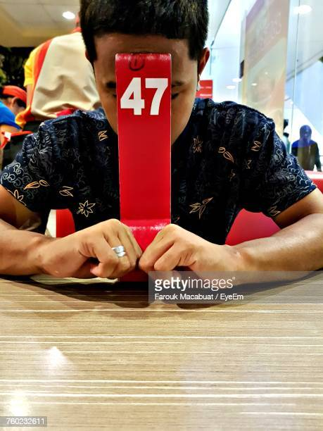 Man Waiting For Order While Sitting On Chair At Restaurant
