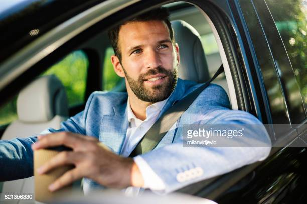 Man waiting in the car and drinking coffee