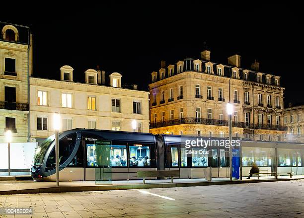 man waiting next to new tram in bordeaux - tram stockfoto's en -beelden