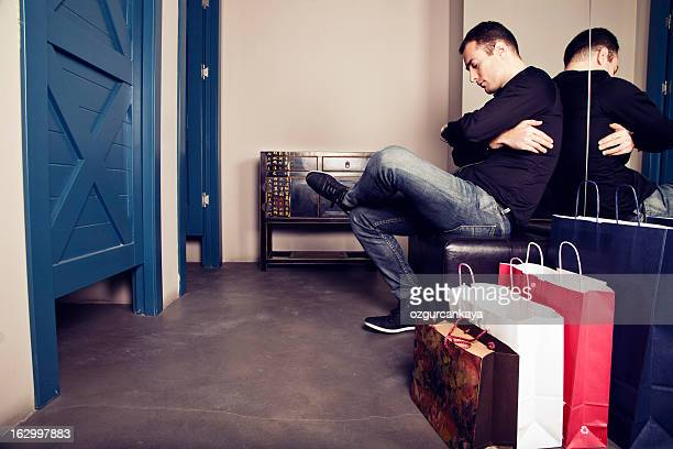 A man waiting outside of a changing room for his wife