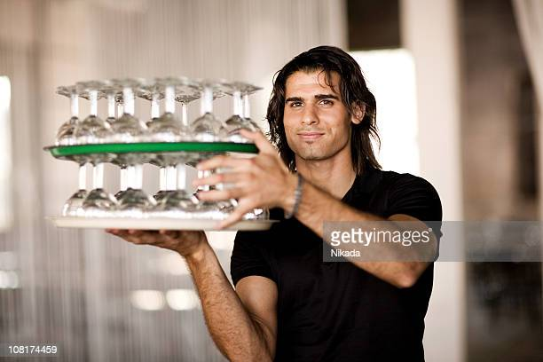 Man Waiting Tables with Empty Wine Glasses