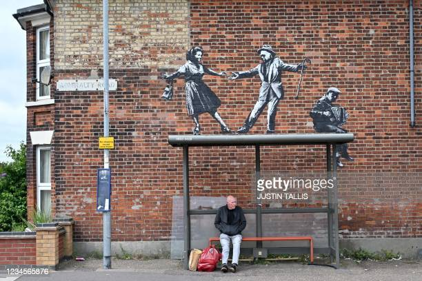 Man waits at a bus stop below a graffiti artwork of a couple dancing to an accordion player, which bears the hallmarks of street artist Banksy, on a...
