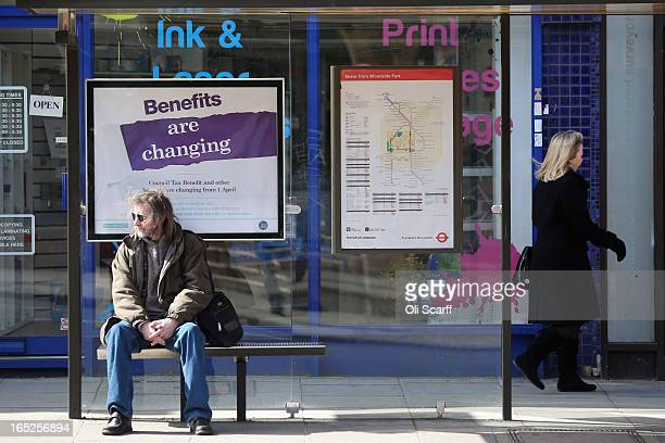 A man waits at a bus stop in North London in front of a poster informing of changes to the benefits and tax system that have come into force...