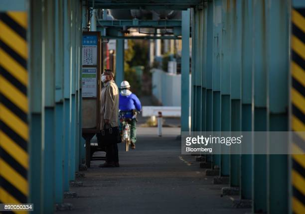 A man waits at a bus stop in the Keihin industrial area of Kawasaki Kanagawa Prefecture Japan on Tuesday Dec 12 2017 The Bank of Japan will release...