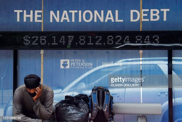 Man waits at a bus stop that displays the national debt of the United States on June 19, 2020 in Washington, DC.