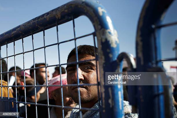 A man waits behind a fence to cross from Syria into Turkey on the border September 30 2014 near Suruc Turkey Kurdish troops are engaged in a battle...