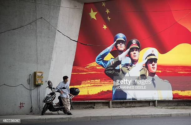 A man waits beside his electric scooter as he charges it next to a Chinese military recruitment poster in Shanghai on July 29 2015 AFP PHOTO /...