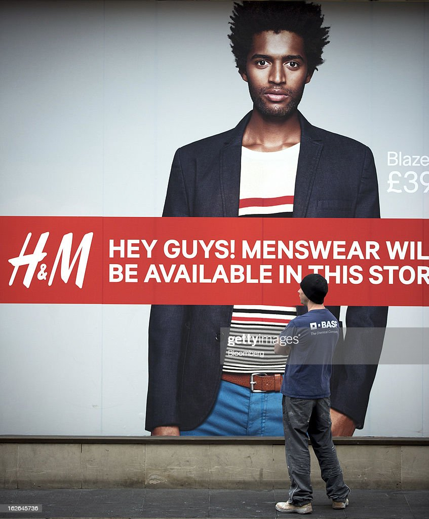 A man waits by a giant poster for the clothing store Hennes & Mauritz AB (H&M) on Oxford Street in central London, U.K., on Monday, Feb. 25, 2013. U.K. Chancellor of the Exchequer George Osborne won't bow to opposition calls to change economic plans after the decision by Moody's Investors Service to strip the U.K. of its Aaa status. Photographer: Jason Alden/Bloomberg via Getty Images