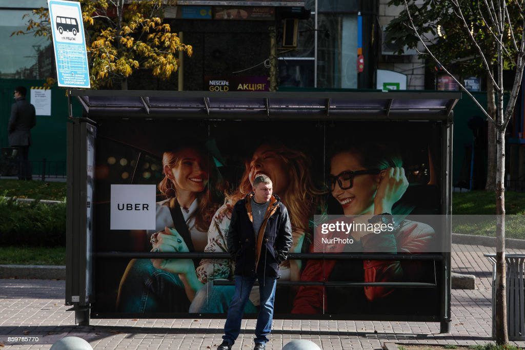 A man waits for a bus at the bus stop branded with Uber Taxi service ad at Khreshchatyk str. in Kyiv, Ukraine, October 10, 2017.
