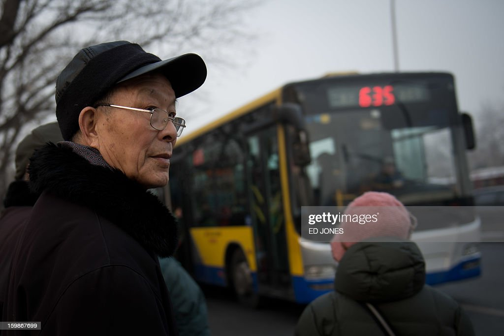 A man waits for a bus beside a busy road in Beijing on January 22, 2013. Beijing has the worst traffic jams in the world, as record traffic levels take their toll on people's health, productivity and social lives, a study by IBM reported early January. Beijing and Mexico City scored 99 out of 100 in IBM's commuter pain index, followed by Johannesburg, Moscow and New Delhi. AFP PHOTO / Ed Jones