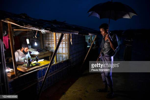 A man waits for a tailor to fix his clothes August 28 2018 in Balukhali refugee camp Cox's Bazar Bangladesh UN investigators said on Monday that...
