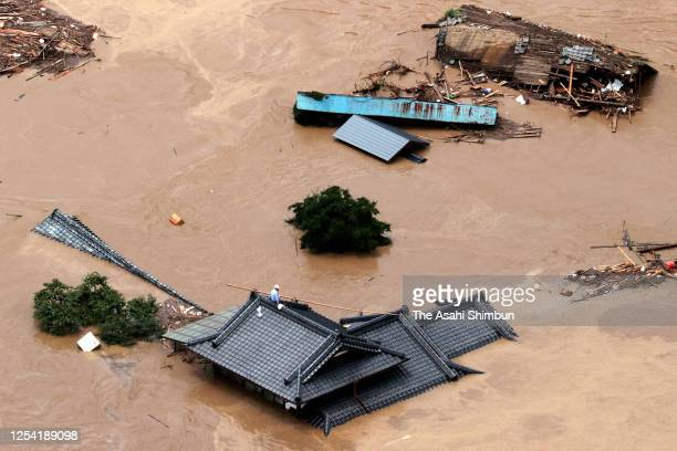 Man waits for being rescued on a roof of a house after the area is inundated after torrential rain triggered flood of Kumagawa River on July 4, 2020...